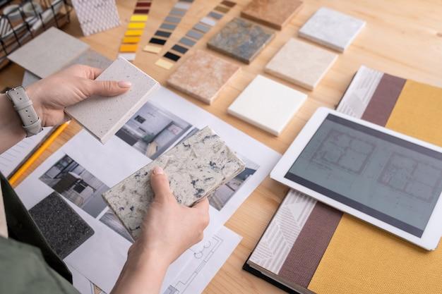 Handen van jonge vrouwelijke ontwerper met twee monsters van marmeren tegels over houten tafel met digitale tablet, foto's van interieur enz
