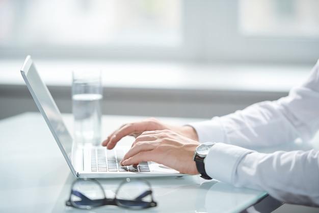 Handen van jonge zakenman in wit overhemd toetsen van toetsenbord aan te raken tijdens het gebruik van laptop voor het organiseren van werk
