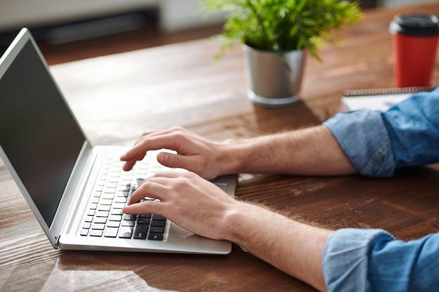Handen van jonge zakenman of ontwerper aanraken van knoppen van laptop toetsenbord tijdens netwerken door tafel