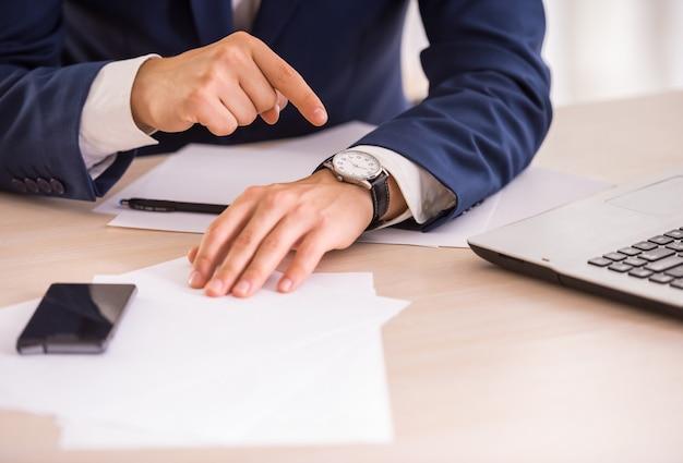 Handen van jonge zakenman wijst op het horloge.
