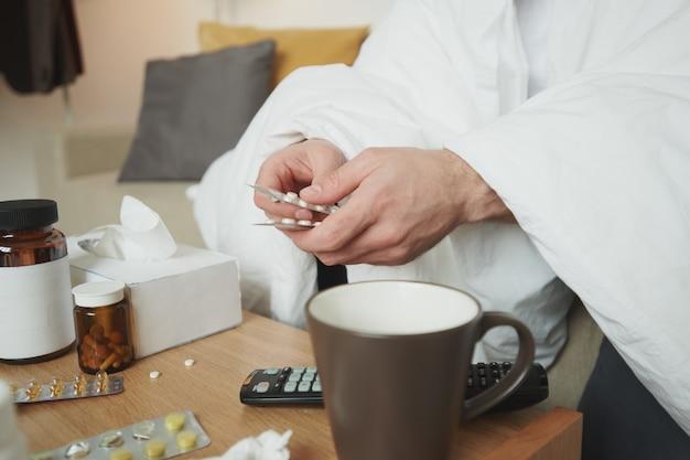 Handen van jonge zieke man onder deken zitten door kleine tafel met verschillende medicijnen en tablet te nemen terwijl thuisblijven
