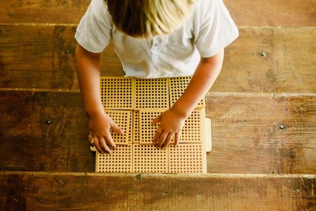 Handen van jongen die tellende kubussen op houten achtergrond in montessoriklaslokaal manipuleren