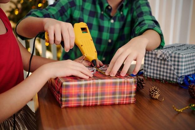 Handen van jongen die zus helpt om klatergoudstrik op ingepakt kerstcadeau te lijmen