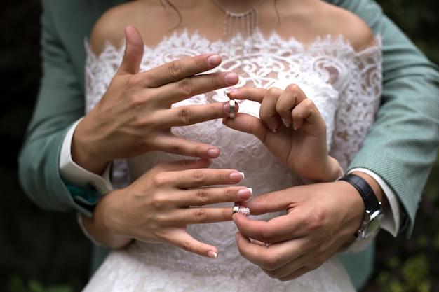 Handen van jonggehuwden die trouwringen op elkaar close-up zetten