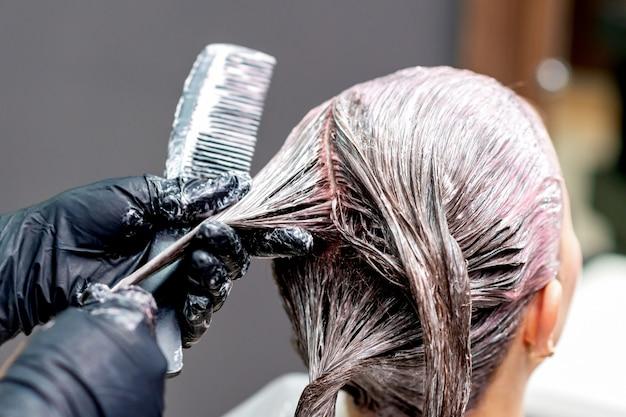 Handen van kapper verven haar van vrouw, close-up.