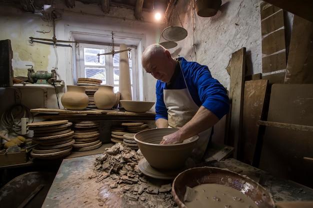 Handen van keramische kunstenaar die een stuk maken