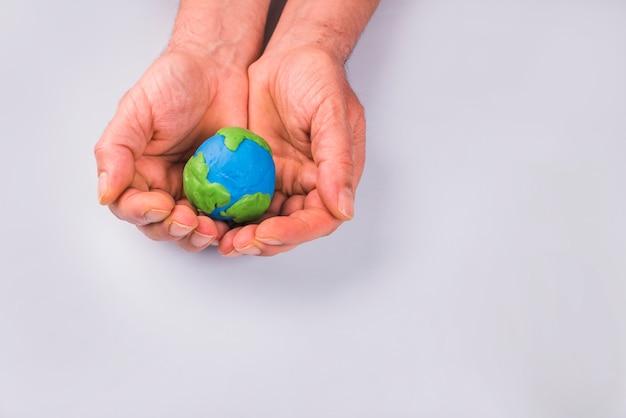 Handen van kind die kleurrijk kleimodel van aarde houden