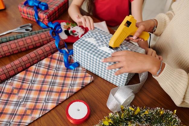 Handen van kinderen die lijmpistool gebruiken bij het inpakken van kerstcadeaus in geruit papier