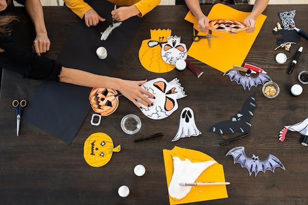 Handen van kinderen en jonge vrouw die halloween-papiersymbolen maken