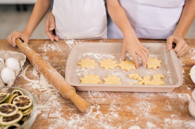 Handen van kleine jongen met deegroller rauwe cookie aanbrengend lade terwijl moeder helpen met het maken van cookies