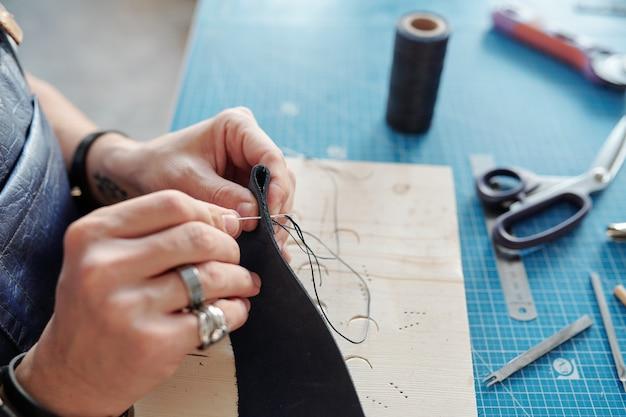 Handen van leerbewerker met stuk zwart leer naaien nieuw item terwijl het boven tafel met benodigdheden