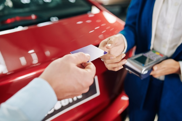 Handen van man die creditcard geeft aan manager bij het betalen voor huurauto Premium Foto