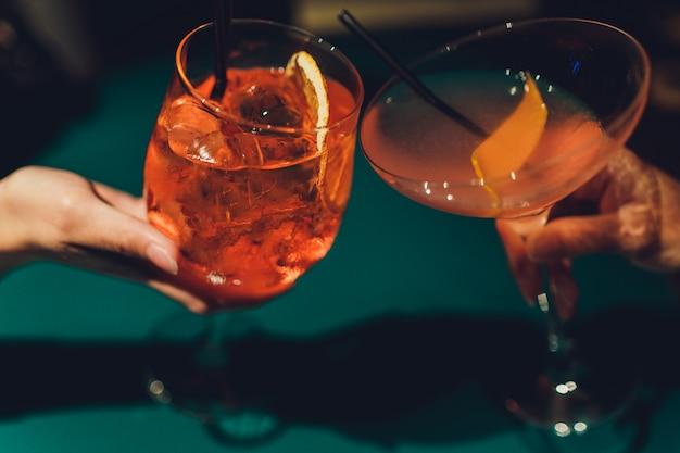 Handen van man en vrouw die met glazen roze champagne toejuichen.