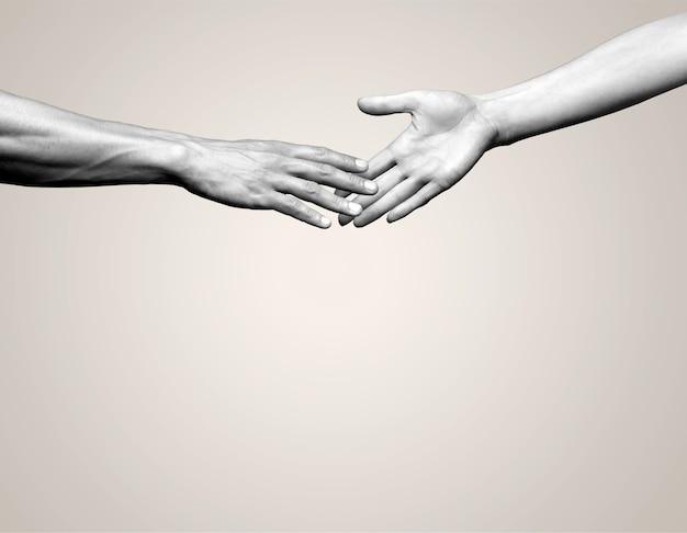 Handen van man en vrouw die naar elkaar reiken