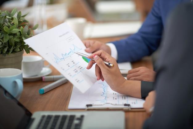Handen van man en vrouw in bedrijfskledijzitting bij bureau in bureau en het bespreken van grafiek