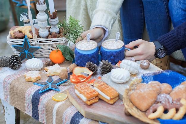 Handen van man en vrouw met mokken met warme drank op tafel met winter decor