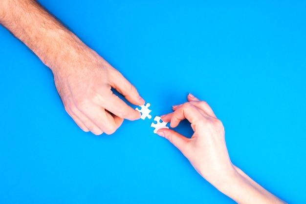 Handen van man en vrouw verzamelen puzzels op een blauwe achtergrond conceptueel beeld van gezamenlijke samenwerking in de familie. uitzicht van boven