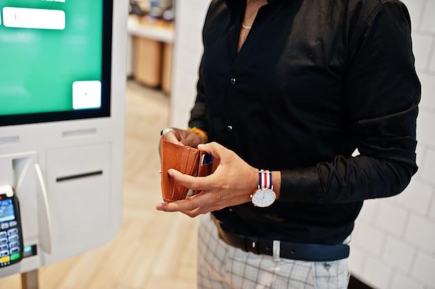 Handen van man klant bij winkel plaatst bestellingen en betaalt via zelf betalen vloer kiosk voor fast food, betaalterminal. zijn portemonnee en zoek creditcard.