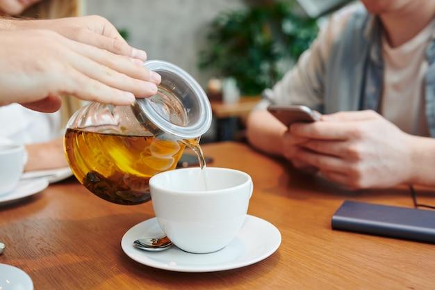 Handen van man met theepot kruidenthee gieten in witte porseleinen beker terwijl tijd doorbrengen in café met universiteitsvrienden