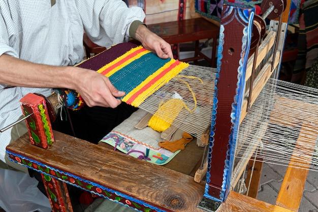 Handen van man wevende stof op een houten weefgetouw. traditionele russische volkskunst. tapijt weefproces.