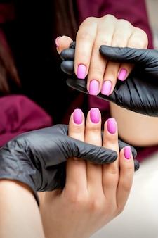 Handen van manicure houdt vrouwelijke vingernagels met roze nagellak in nagelsalon
