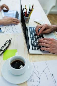 Handen van mannelijke grafisch ontwerper met behulp van laptop
