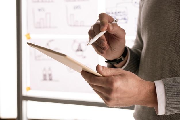 Handen van mannelijke makelaar of econoom met pen wijzend op touchpad-display terwijl staande tegen whiteboard