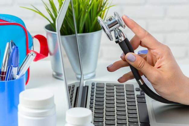 Handen van medische artsenvrouw met laptop.