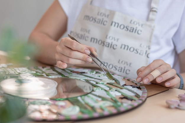 Handen van meester bezig met nieuwe moderne kleurrijke mozaïek. detailopname