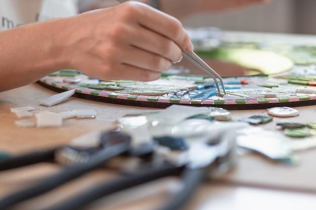 Handen van meester die aan nieuwe moderne kleurrijke mozaïekclose-up werken