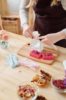 Handen van meisje bindend papier pakket met lint op een houten bord tijdens het inpakken van handgemaakte zeepstaven