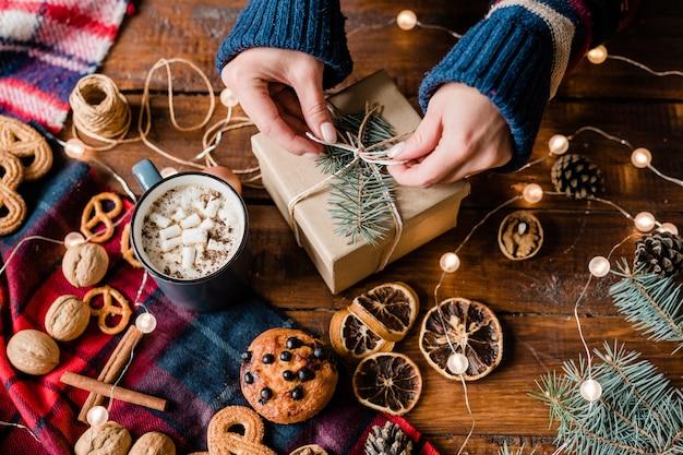 Handen van meisje boog bovenop verpakte geschenkdoos omgeven door zoet voedsel, walnoten, slingers en warme cappuccino in mok