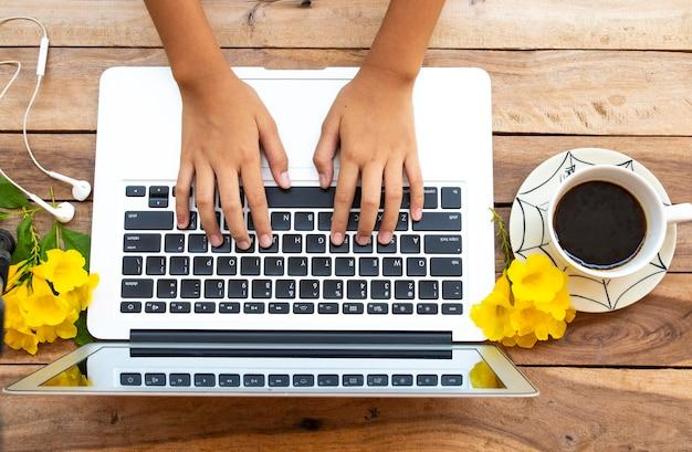 Handen van meisje dat aan computer werkt