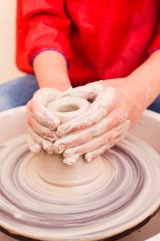 Handen van meisje dat aardewerk probeert te maken van witte klei op een pottenbakkersschijf