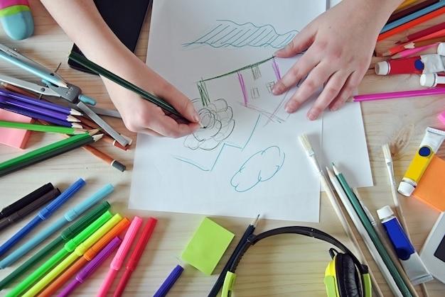 Handen van meisje die een afbeelding op je bureaublad schilderen