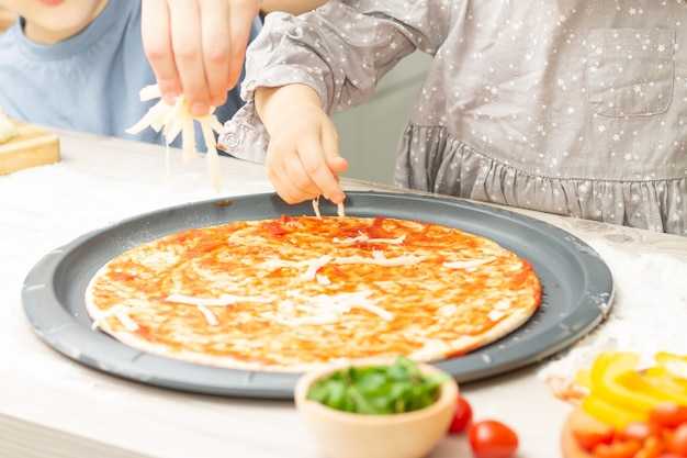 Handen van meisje in grijze jurk en jongen pizza samen koken in de keuken. broer en zus koken