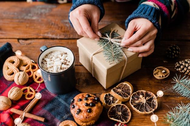 Handen van meisje knoop bovenop verpakte geschenkdoos omgeven door zoet eten, warme drank in mok en walnoten