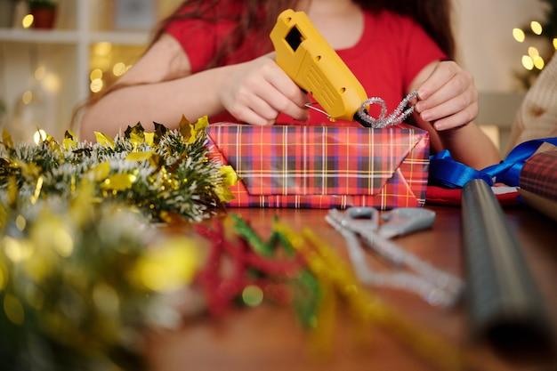 Handen van meisje lijmen klatergoud strik op verpakt cadeau met heet lijmpistool