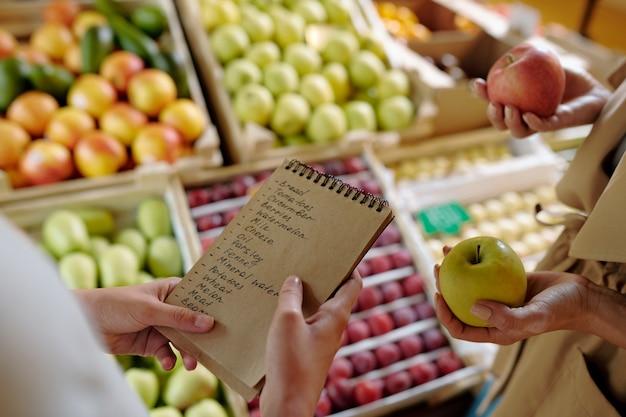Handen van meisje met kladblok met boodschappenlijst door display met pruimen, peren en perziken