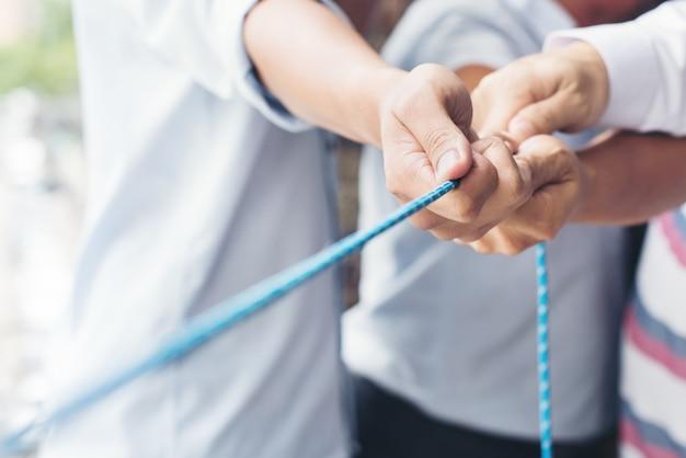 Handen van mensen die aan het touw trekken
