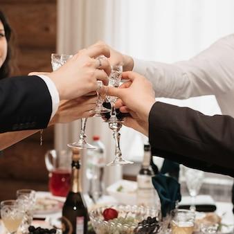 Handen van mensen rammelende glazen wijn tijdens een vakantie in een restaurant