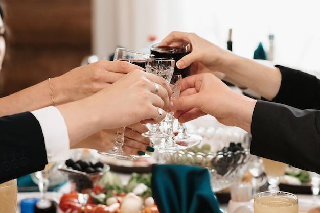 Handen van mensen roosteren en rammelende glazen tijdens een feest in een restaurant