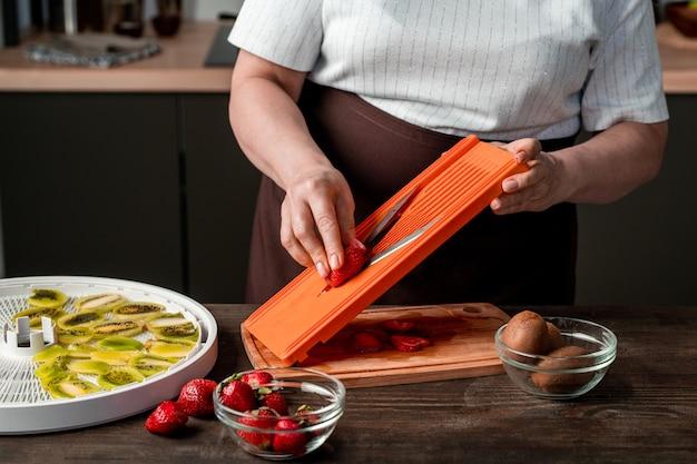 Handen van moderne huisvrouw met snijder verse aardbeien hakken over houten bord om ze op dienblad van fruitdroger te zetten