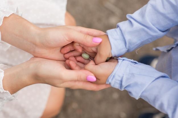 Handen van moeder en baby. licht beeld. groene bes