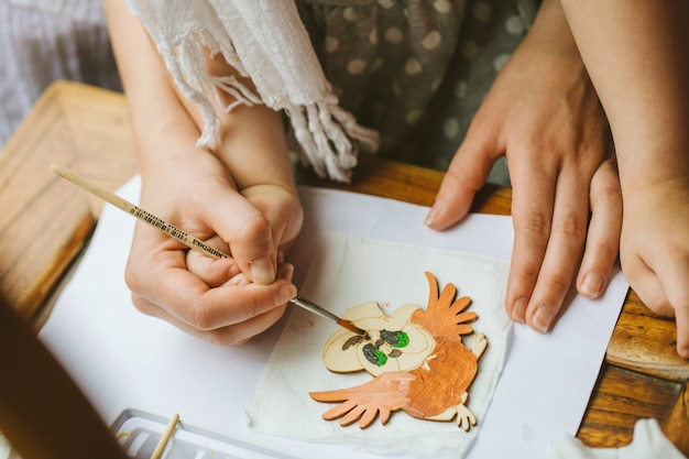 Handen van moeder en kind, die samen met een penseel met verf op een houten spatie tekenen. moeder helpt het kind de verf voorzichtig aan te brengen.