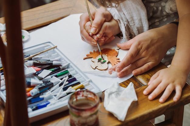 Handen van moeder en kind, die samen met een penseel tekenen