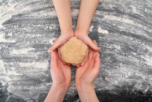 Handen van moeder en kind zijn met deeg. koekjes koken met kinderen, samen tijd doorbrengen. bovenaanzicht.