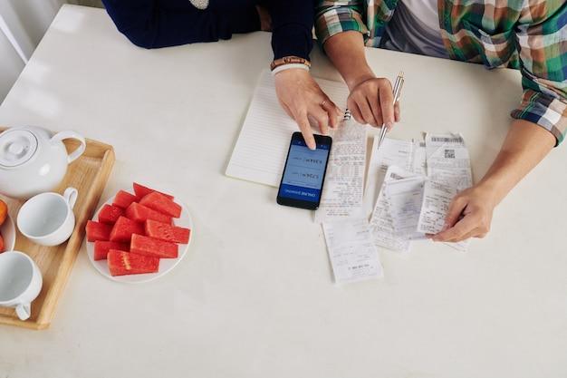 Handen van moeder en zoon die rekeningen betalen via bankapplicatie op smartphone, uitzicht vanaf de top
