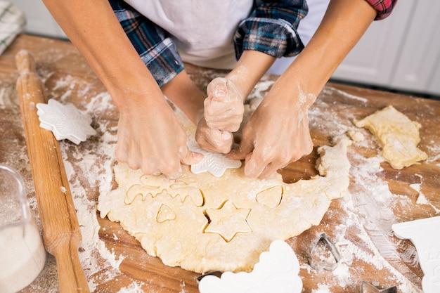 Handen van moeder en zoon koekjes van gerold deeg snijden tijdens het koken van gebak voor het kerstdiner