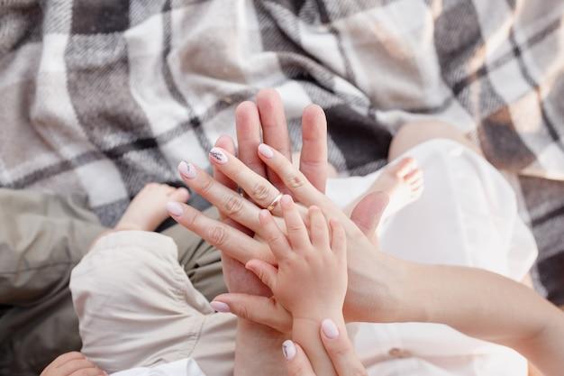 Handen van moeder, vader en zoontje